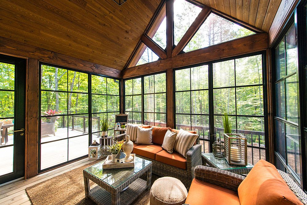 Smart sunroom with breezy decor is connected with the deck outside [Design: Linwood Custom Homes]