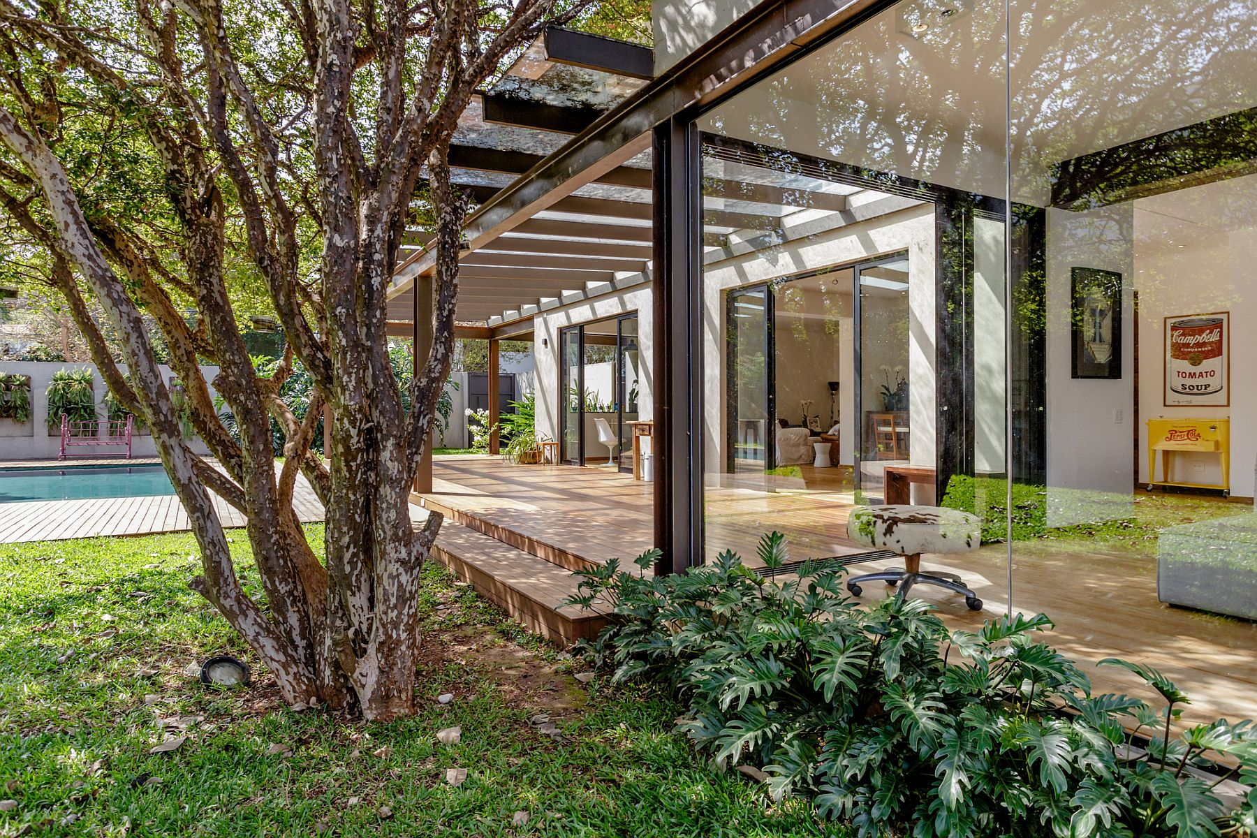 Steel structure of the house along with glass walls blurs the boundary between the interior and the world outside