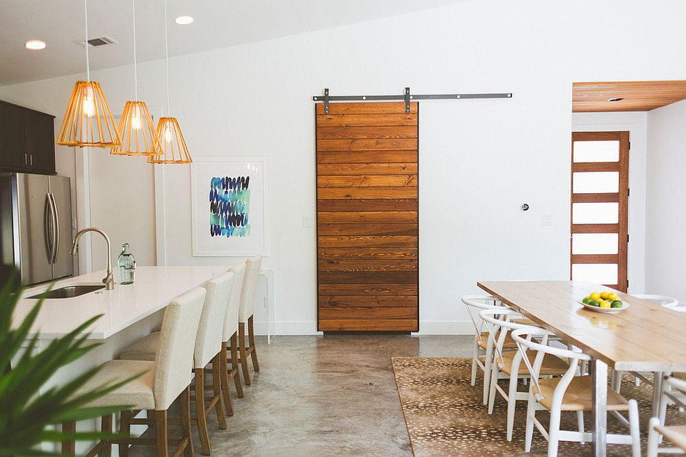 Striking sliding barn door hides the pantry in this kitchen and dining space