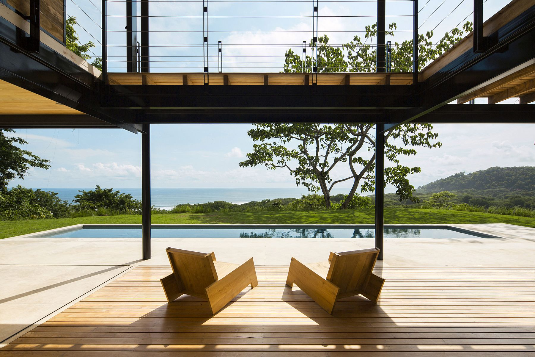 Sweeping wooden terrace and interior opens up to the ocean and jungle views outside