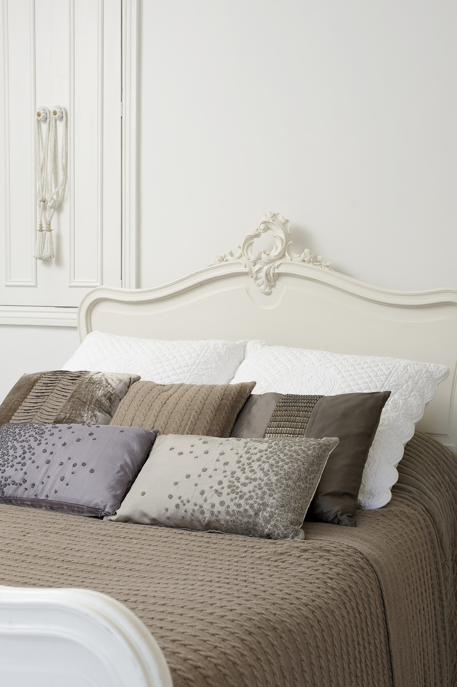 Taupe bedding offsets white walls