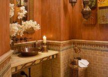 Unique decorative pieces on the wall, Moroccan style lighting and textured walls for the Mediterranean powder room