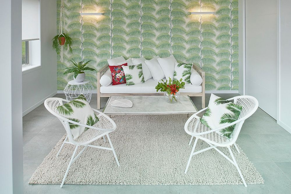 Wallpaper with bold tropical leaf motif creates the ideal backdrop for a relaxing sunroom