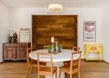 Wooden accent feture in the backdrop brings warmth and contrast to the dining room in white