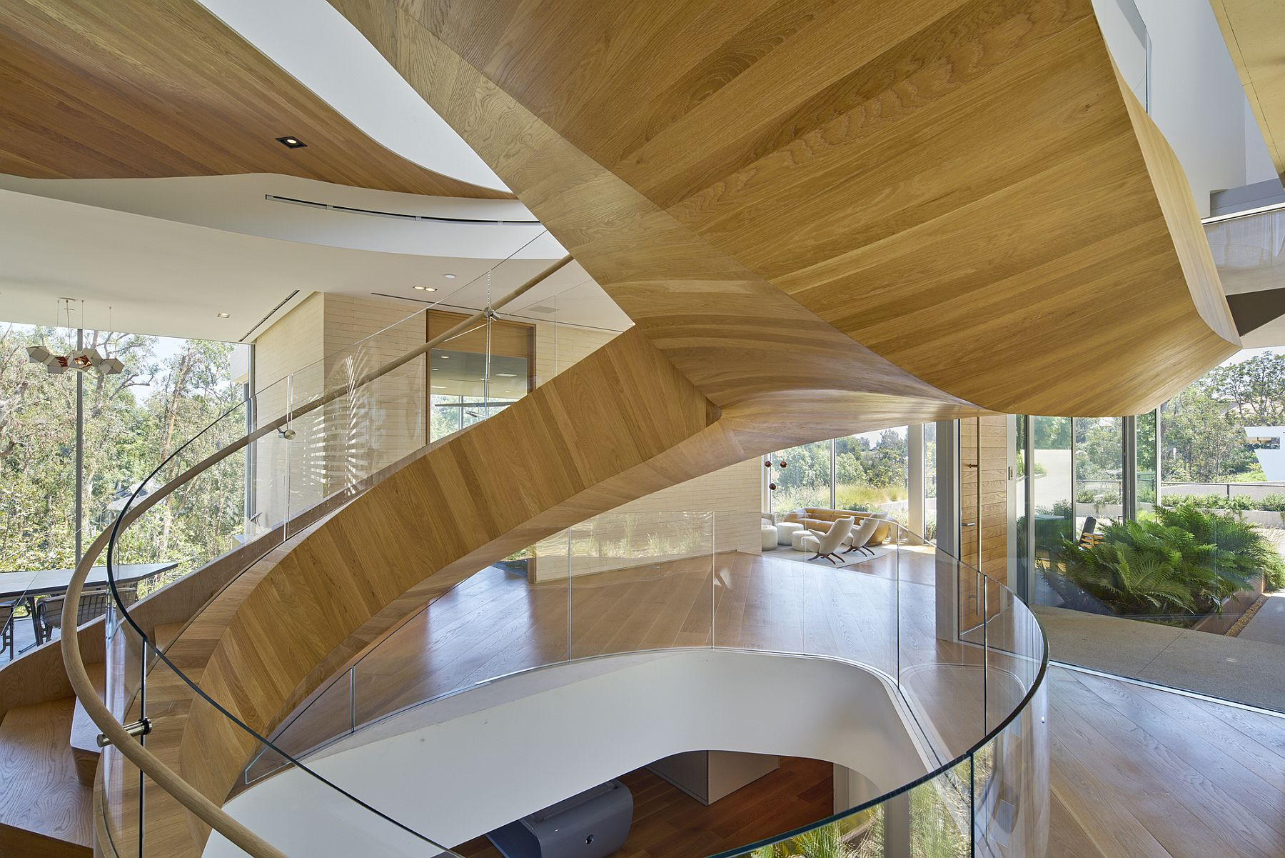 Amazing curvy staircase delineates spaces and adds extravagance to the interior