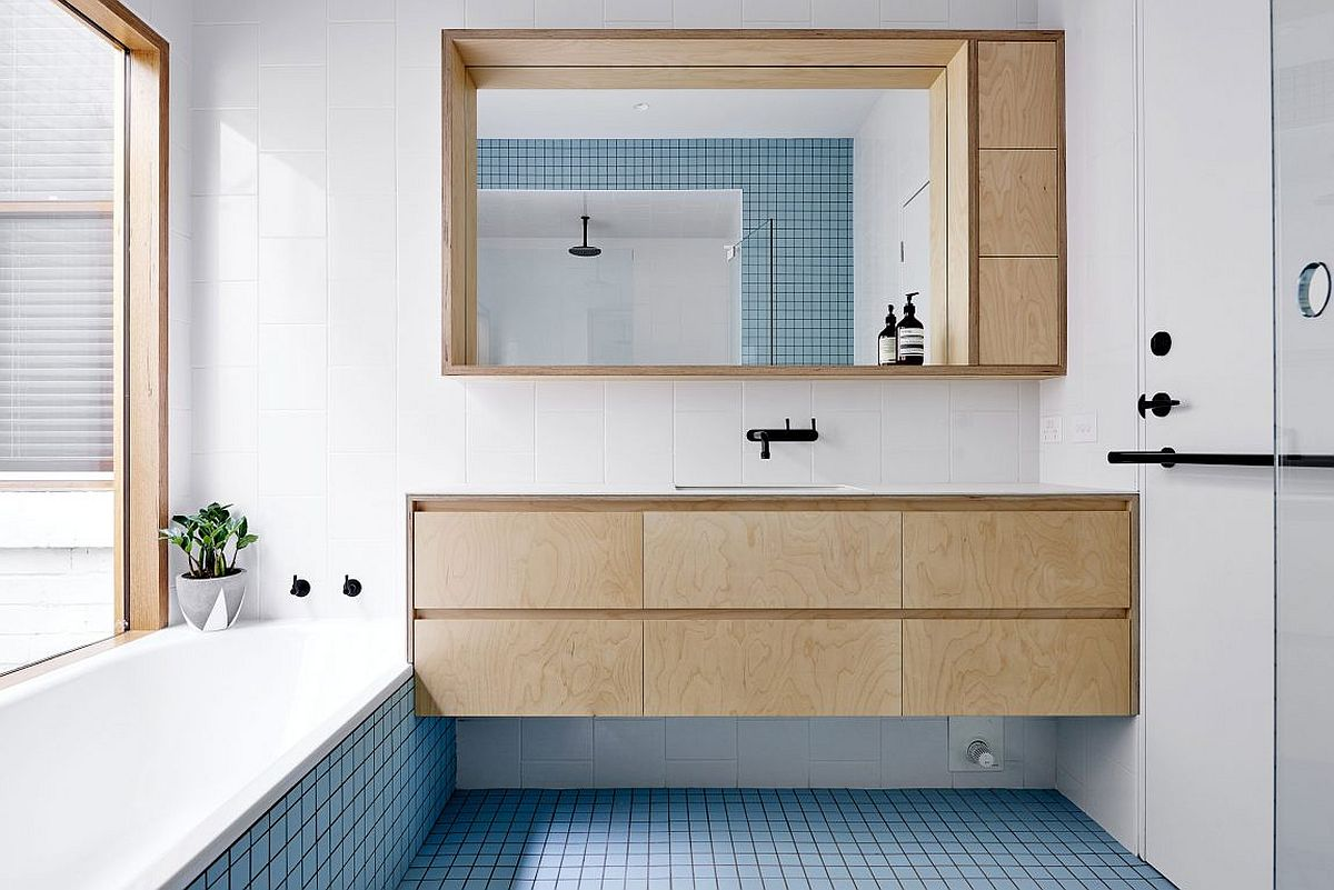 Beautiful blue tiles energize the contemporary bathroom in white