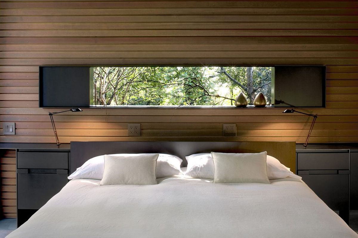 Bedroom with a window above the headboard that offers a view of the outdoors