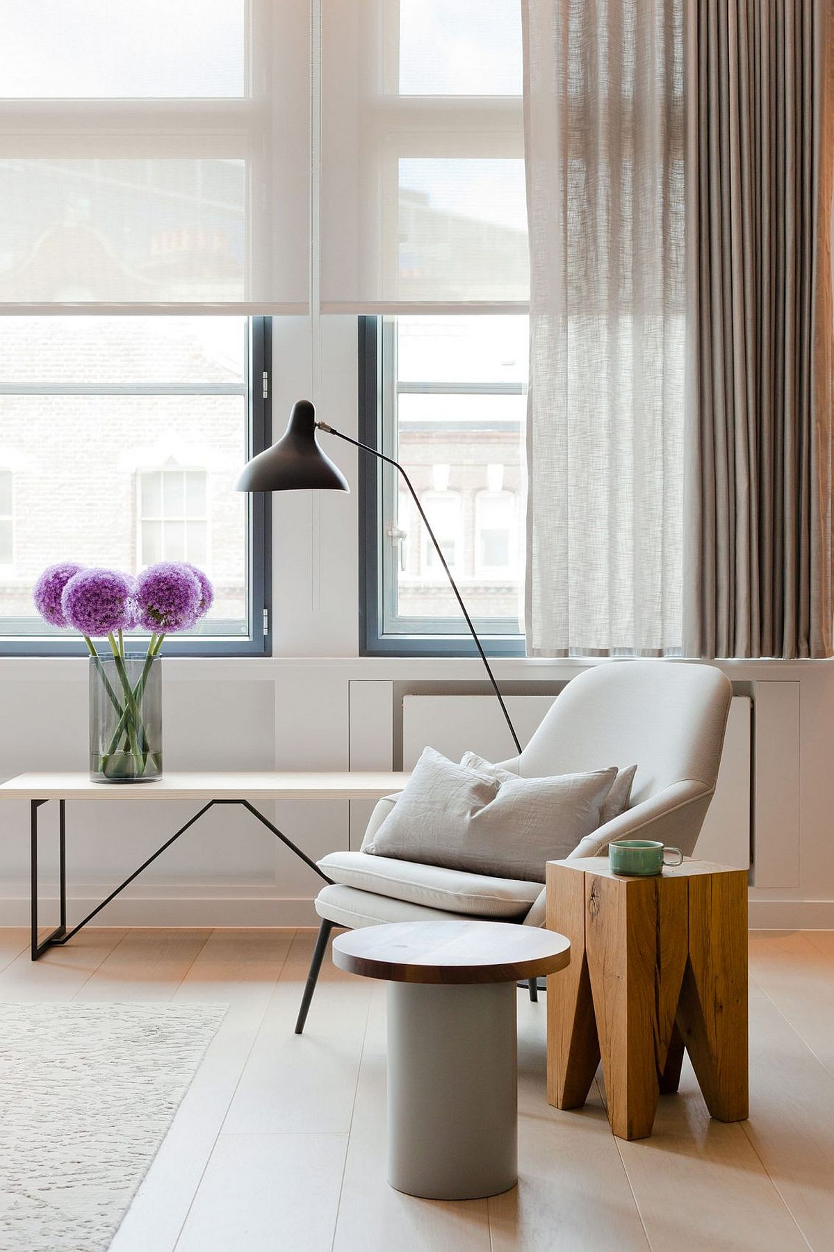 Comfy chair in white and wooden side table for the elegant living room of London penthouse