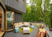 Contemporary deck with luxurious seating, string lighting and a forest view