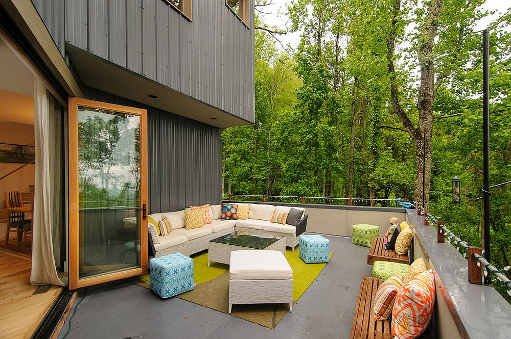 Contemporary deck with luxurious seating, string lighting and a forest view [Design: Smart Builders, Inc]