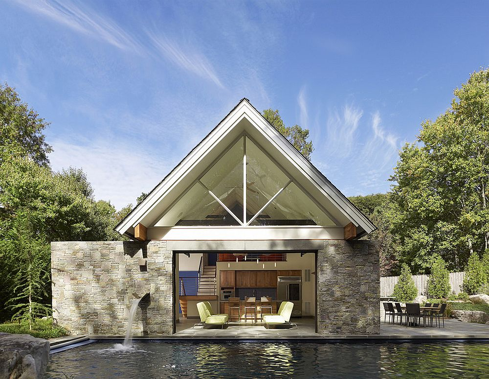 Contemporary pool house with glass garage door sits tight on the edge of the pool