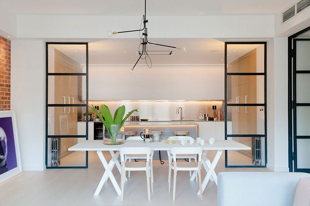 Dining area and kitchen seperated by framed glass partitions with industrial style