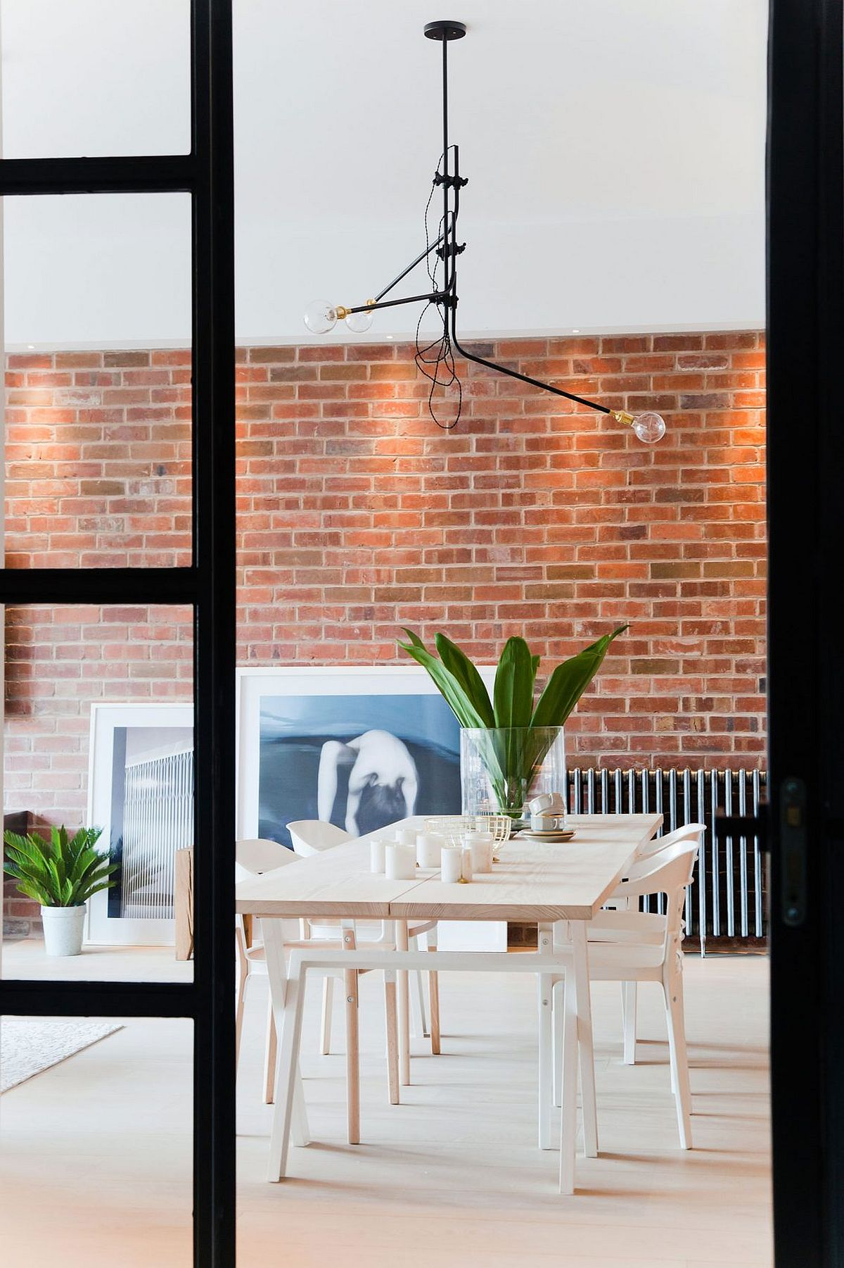 Dining area with industrial style sliding glass doors and brick wall backdrop
