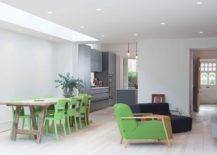 Dining table chairs and club chair give the interior a green glint