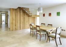 Exquisite reclaimed wood wall with staircase becomes the backdrop in this dining room
