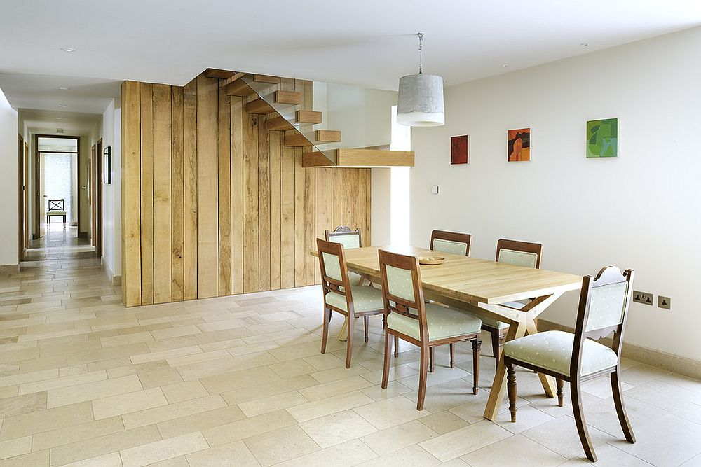 Exquisite reclaimed wood wall with staircase becomes the backdrop in this dining room [Design: PAD studio]