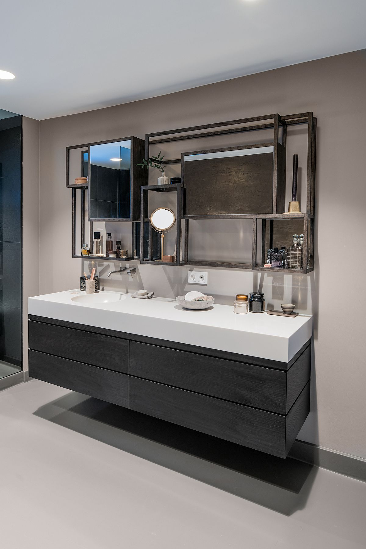 Floating vanity with smart shelving above it is the showstopper in this sleek contemporary bathroom