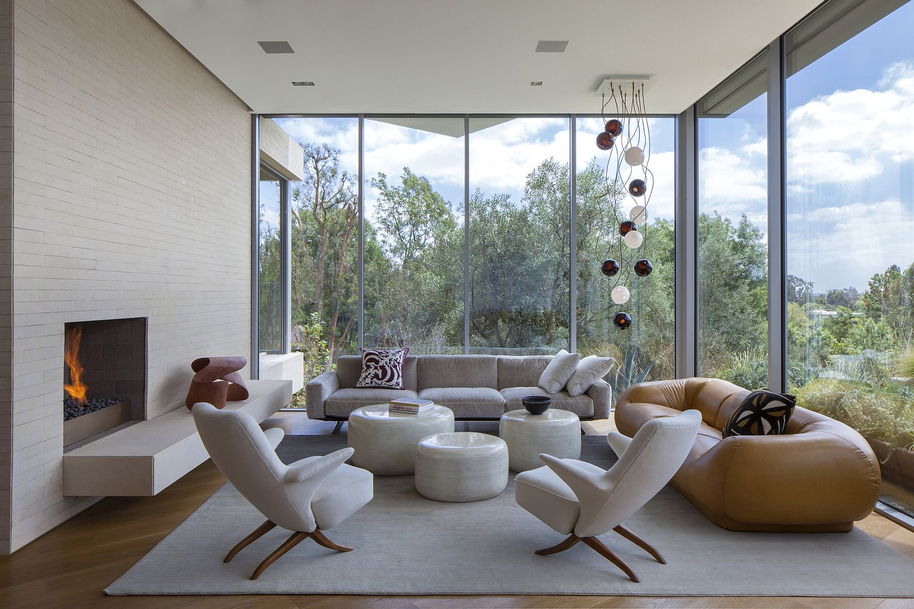 Floor-to-ceiling glass walls offer unabated views of the green valley below