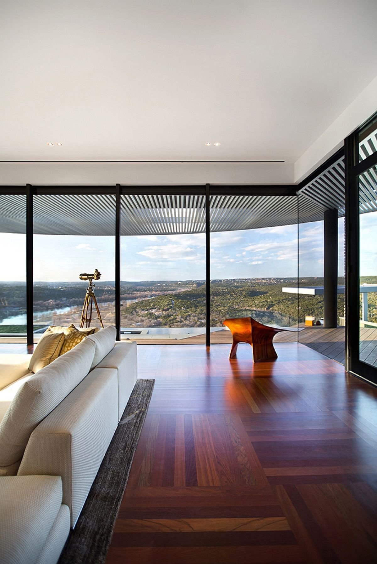 Floor-to-ceiling glass window offer a stunning view of Lake Austin and the rolling hills