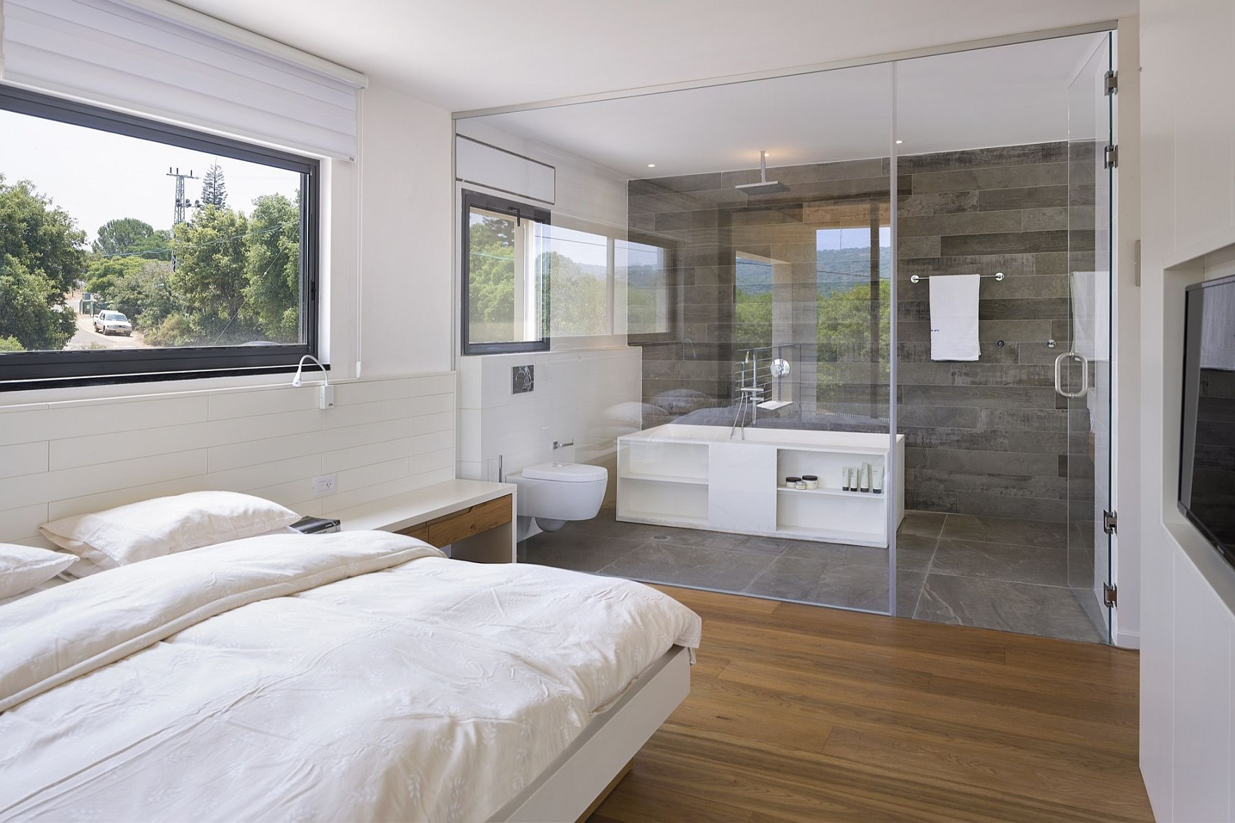 Glass wall seperates the bedroom from the bathroom