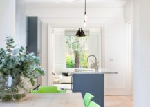 Gorgeous new kitchen with an island in blue offers a view of the living room and the garden