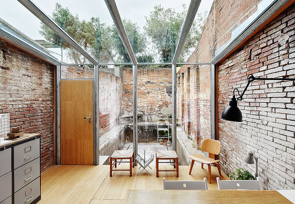 Modern industrial sunroom with lovely brick walls and a glass ceiling [Design: Sauquet Arquitectes i Associats / Photography: José Hevia]