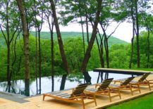 Modern pool and deck overlook mountains and the lush green forest
