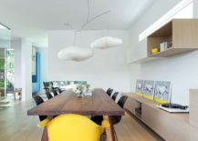 Pendant lights and the yellow chair give the dining space a whimsical appeal