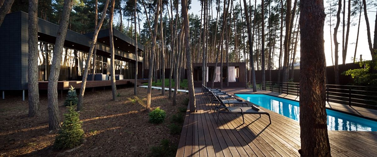 Pool area and deck next to the modern chalet surrounded by tall pine trees