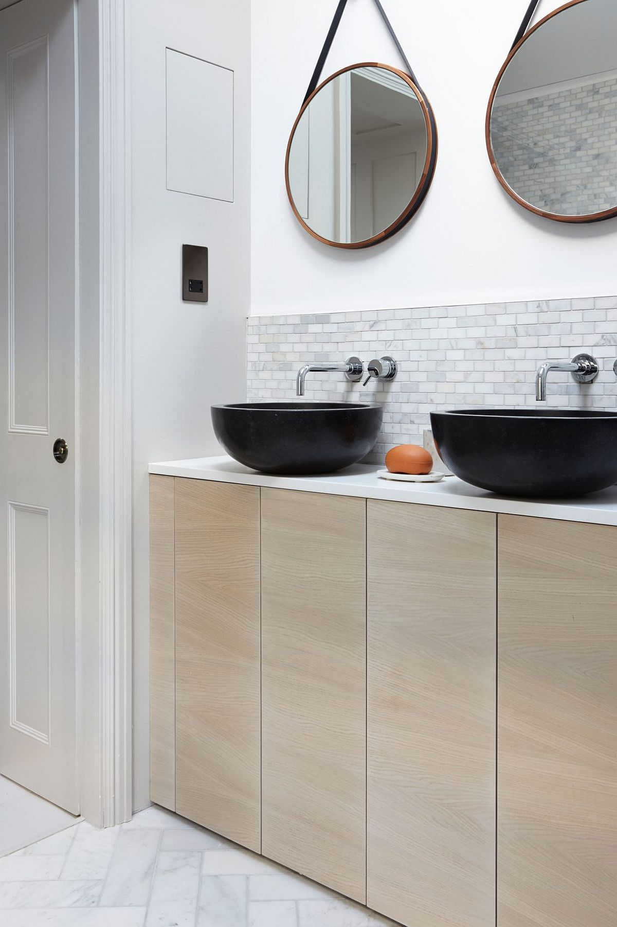 Round mirrors like the ones in this bathroom are a hot trend that also add geo style