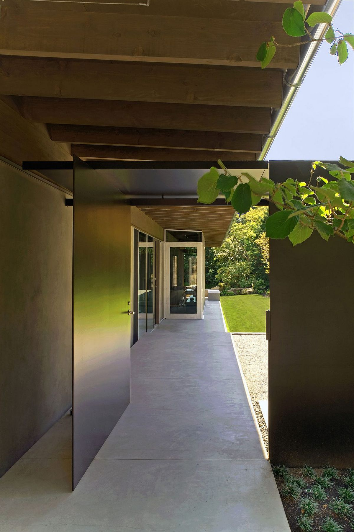 Sheltered terraces and outdoor spaces connect the interior with the lush green landscape around it