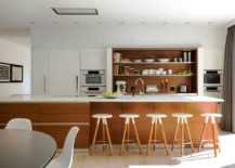 Shelves, kitchen island and bar stools bring warmth of wood to the contemporary living area