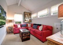 Small beach style media room with bright red couch and coastal themed decor
