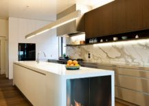 Stylish contemporary kitchen with fireplace built into the island