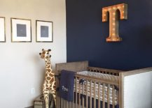 Stylish industrial nursery with dark blue accent wall and illuminated letter on the wall