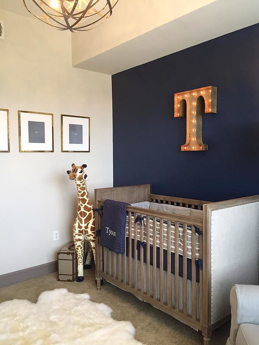 Stylish industrial nursery with dark blue accent wall and illuminated letter on the wall [Design: Mill House Design]