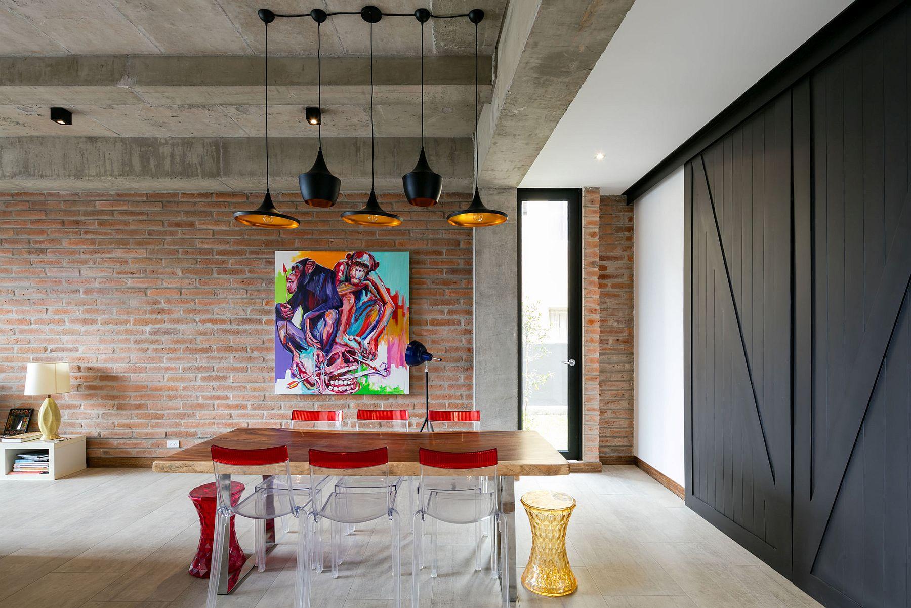 Tom Dixon pendant lights illuminate the industrial modern dining room