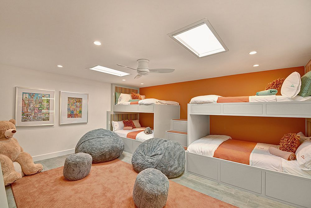 Wall of bunk beds in orange for the kids' room [Design: Bighorn Custom Builders]