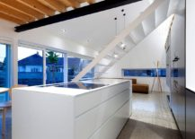 White kitchen island and dark kitchen wall in the open plan living area
