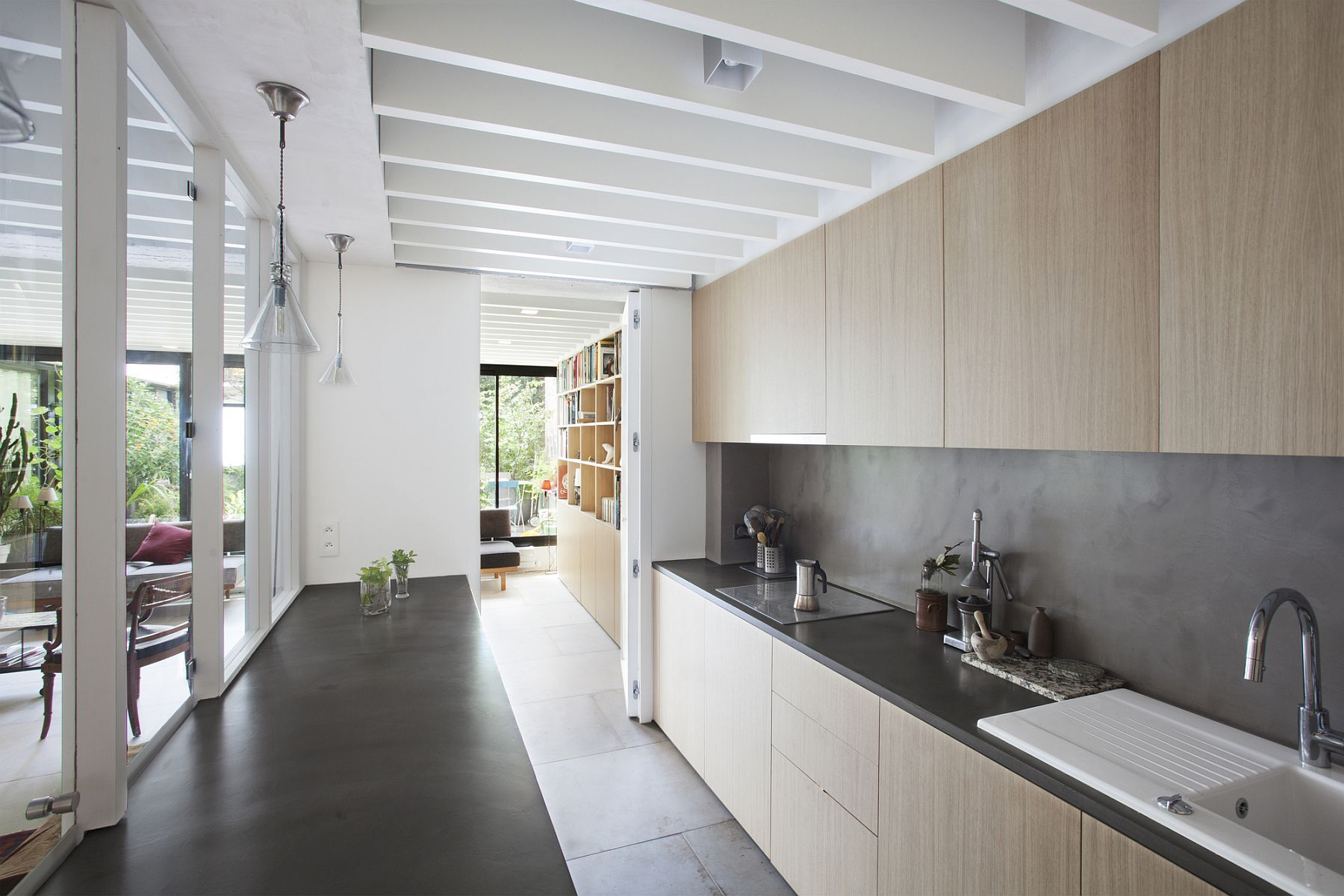 Wooden cabinets and dark kitchen countertops shape the stylish kitchen