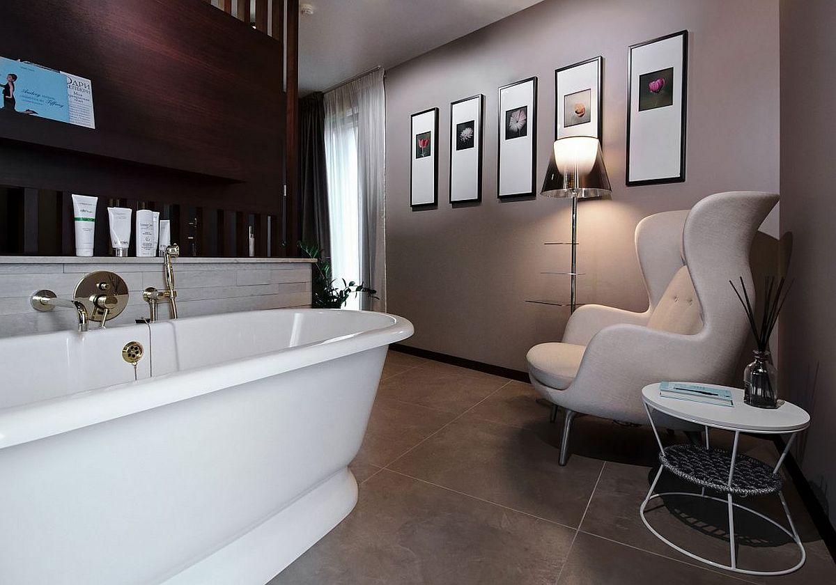Art deco influences for the contemporary bathroom with freestanding bathtub, side table and cozy chair