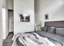 Bedroom in white and gray with small bathroom next to it