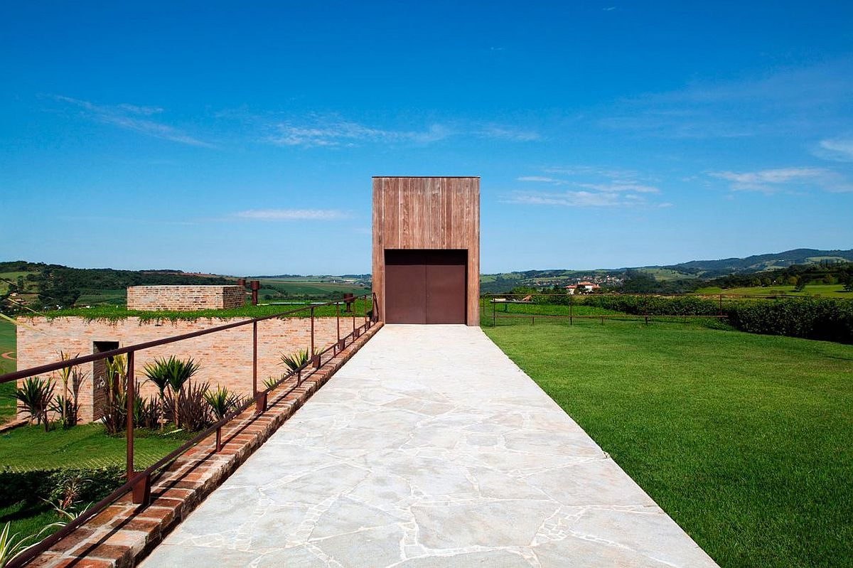 Brazilian teak structure and corten steel door create a unique and striking entrance for the house Hidden from View: Modern Country House Becomes One with the Landscape