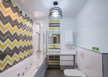 Chevron patterned tile design in yellow and gray create a striking bathroom