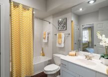 Curtain with chevron stripes brings yellow to the modern gray bathroom