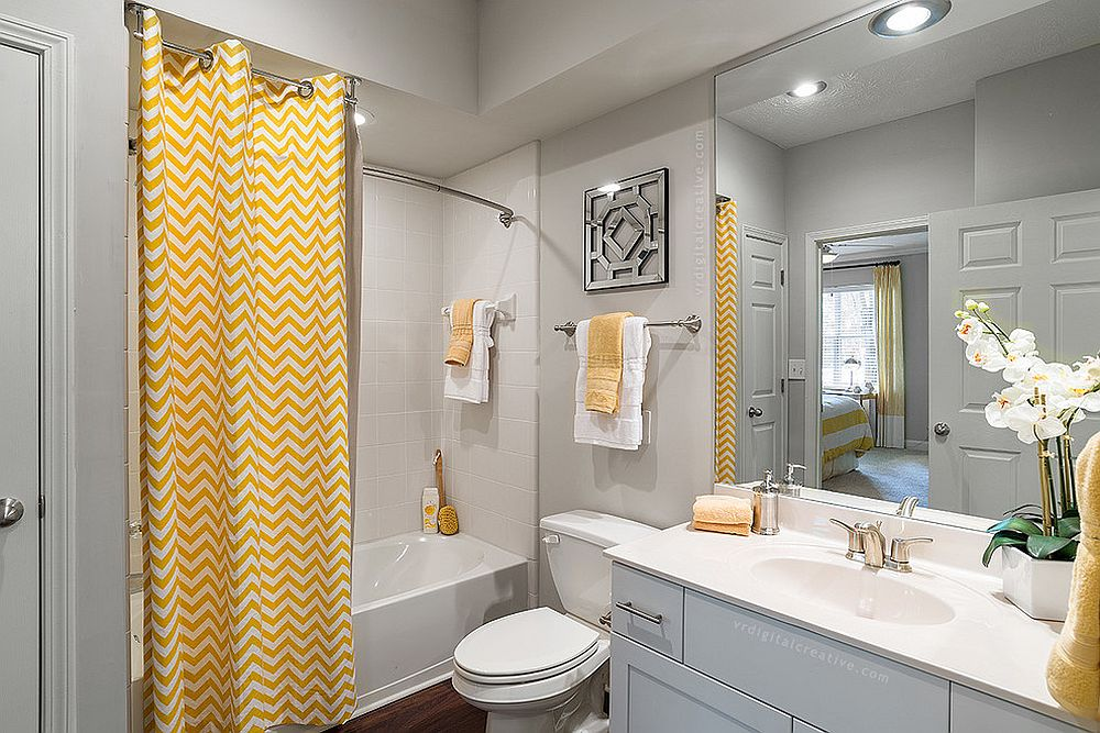 Curtain with chevron stripes brings yellow to the modern gray bathroom [Photo Credit: Valerie Ryan Photography / RealPage, Inc]