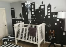 Custom wall mural in the nursery depicts a bright city skyline