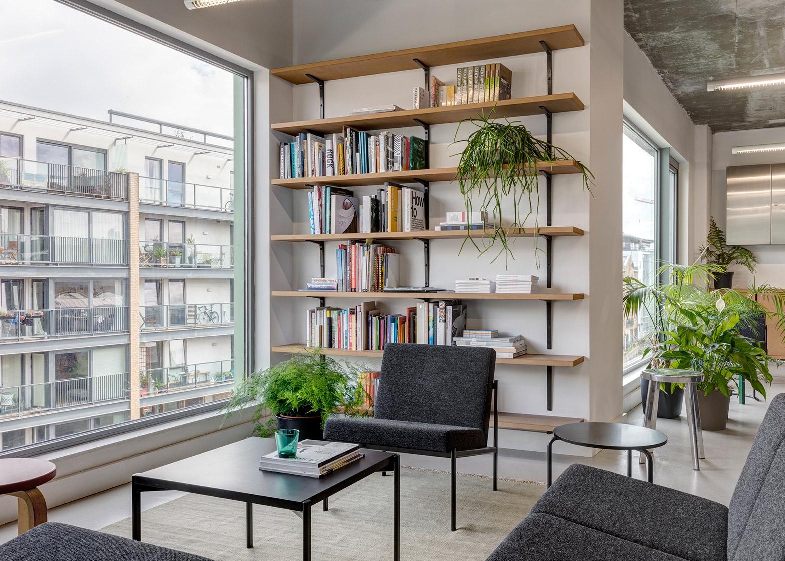 The multi-use lounge area of Dezeen's officeincludesIlmari Tapiovaara's Kiki sofa and armchairs and Aino Aalto's 606 Side Table.Image via Dezeen.