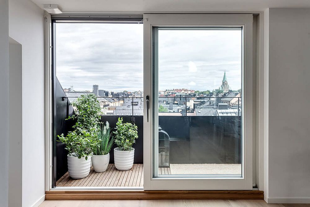 Framed. sliding glass doors connect the attic apartment with the tiny balcony