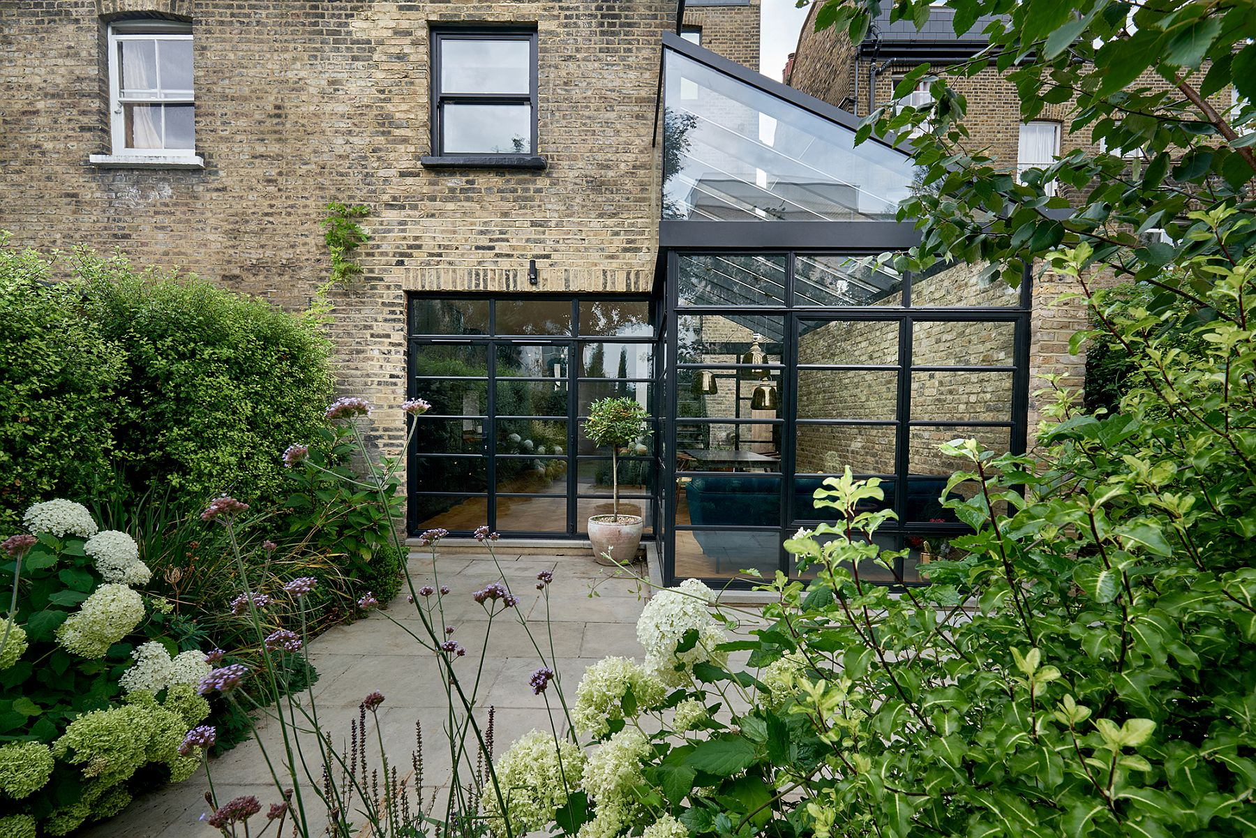 Garden outside becomes a part of the new dining room and kitchen thanks to the glassy extension